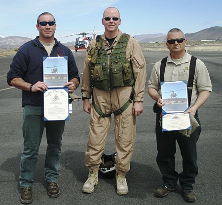 Nevada Division of Forestry Pilot Nick Lopes (left) and Helicopter Manager Lee Stewart (right) receive letters of appreciation from Commander Shane Yates, operations manager at Naval Air Station, Fallon, for their assistance in rescuing skiers near Heavenly, Nevada.